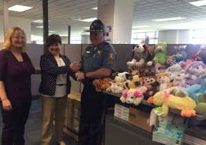 (From left) Lynne Shore and Cindi Hiatt-Henry deliver OSNA's Buddy Bear program donation to Lieutenant Mike Peterson of the Oregon State Police.
